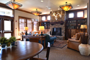 lodge room with fireplace, sitting areas, book shelves, animal motifs