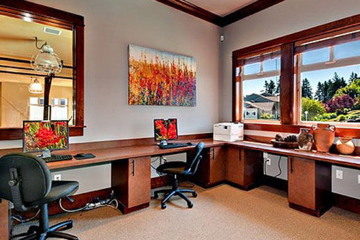 Office room with computer desks, chairs, and nice view of trees outside