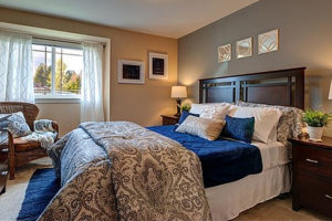 Carpeted bedroom with queen bed, tan walls, bright window