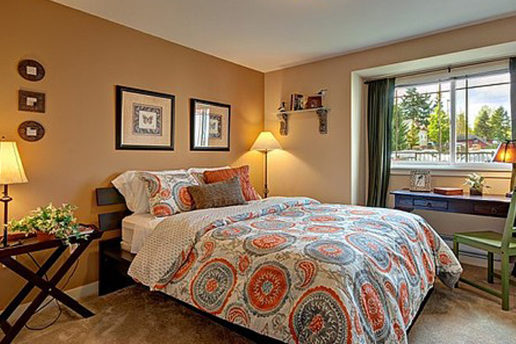 Carpeted bedroom with queen bed, tan walls, decor, and window