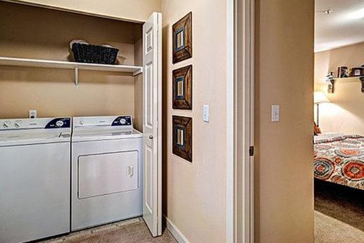 Washer and dryer closet in hallway next to bedroom, white doors