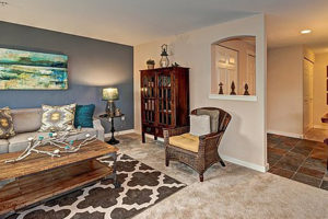 Carpeted living room with blue and cream walls, decor, overlooking foyer with tile floor