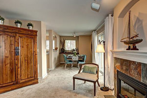 Tile floor foyer entrance to carpeted living room with fire place, natural light