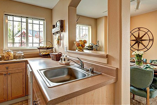 Kitchen sink, natural light, brown countertops, window looking into dining area