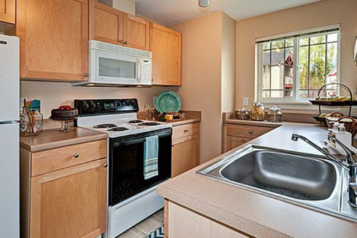 Kitchen, brown cabinetry, white appliances, sink, natural light