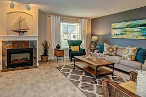 Decorated carpet living room with gray wall, fireplace, couch and chairs