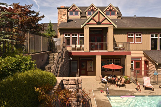 Exterior of building, swimming pool with lounge chairs and family enjoying sun