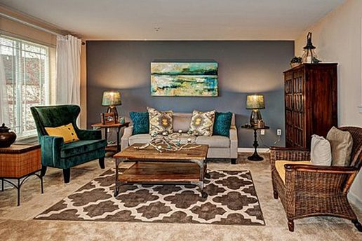Decorated carpet living room with gray wall, couch and chairs